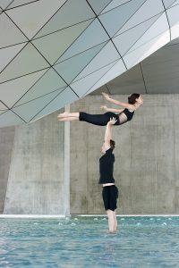 Jonas porte Mathilde en hirondelle au Musée des Confluences. Ils sont debout dans le bassin avec les pieds dans l'eau. Ils s'entrainent à l'AcroYoga avec les AcroGones.